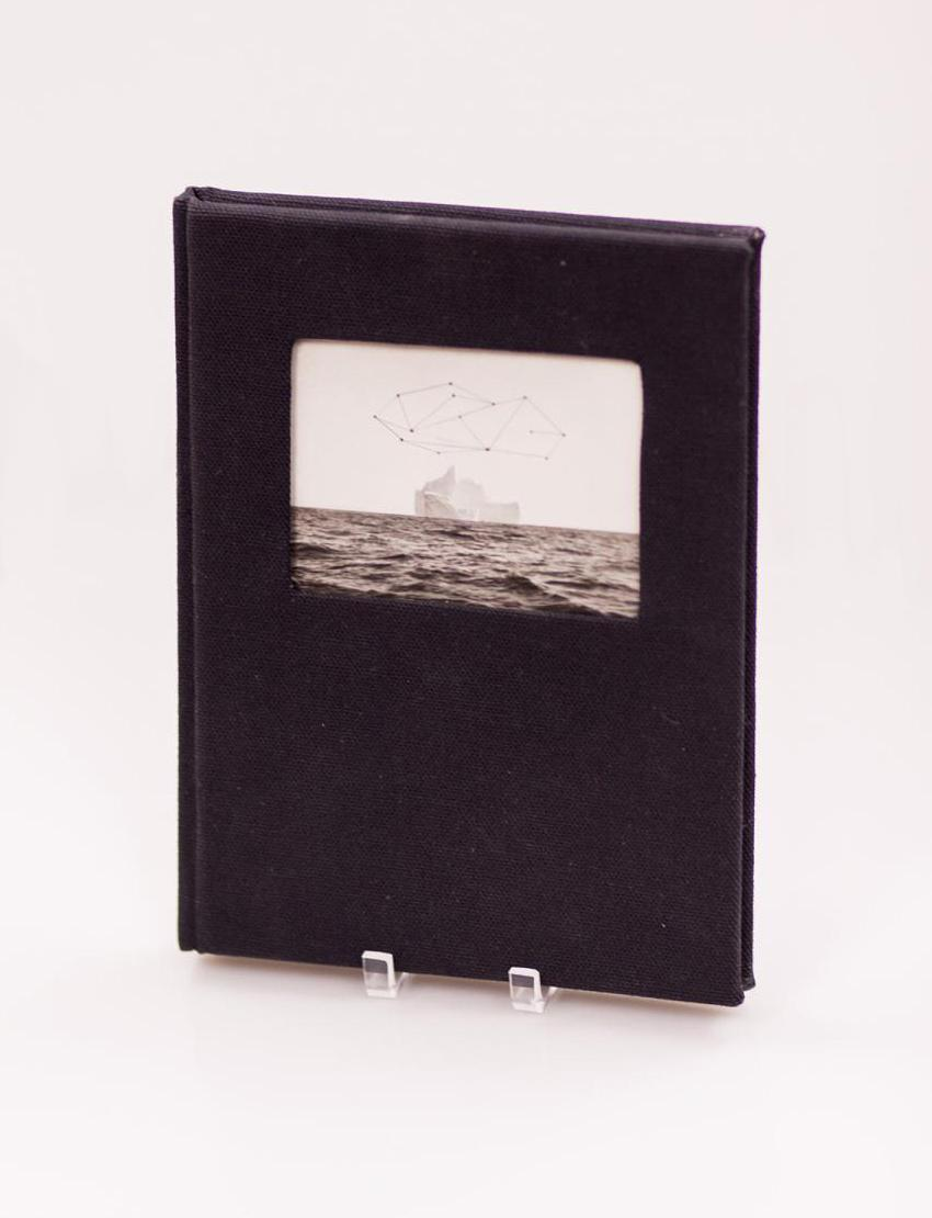 Black book standing upright. On the cover is an old photograph of a body of water on it.