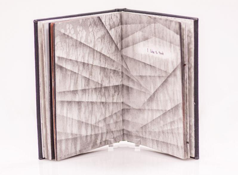 An open book with the pages being a pattern with lines forming different shapes and a cloud-like background.