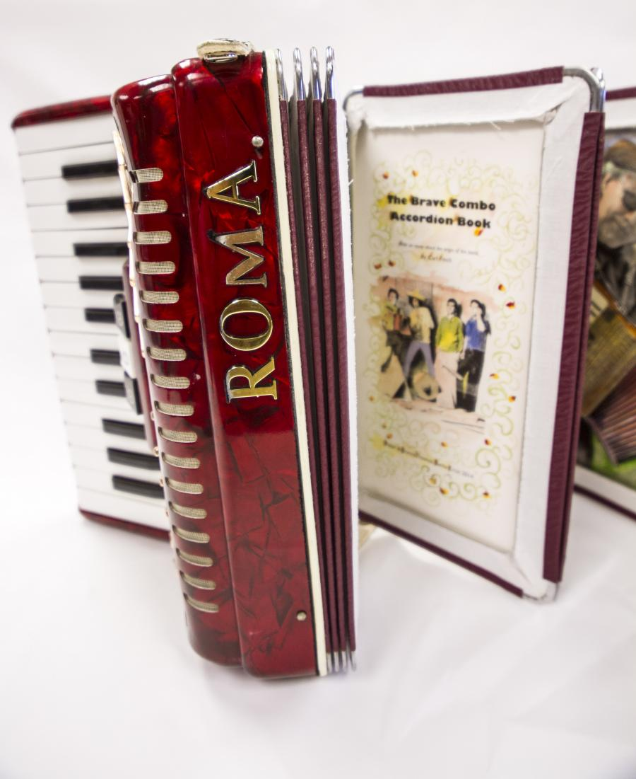 Red accordion with the word Roma on the spine in gold. On the left side is the keyboard part of the accordion and on the right is the title page with the title of the book on it and a drawing of people.