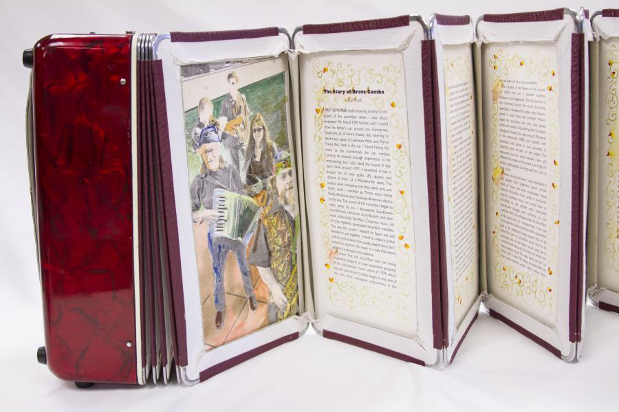 A red accordion extended out into a book, showing multiple pages. The page on the farthest right is a photo and the other pages are filled with text.
