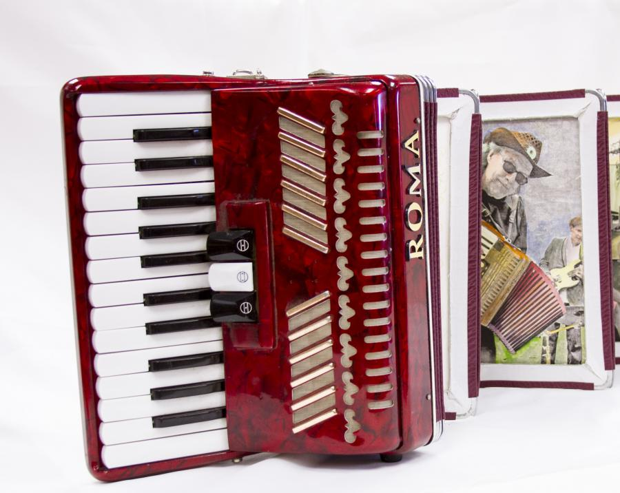 A red accordion with the keyboard part seen on the left and the word Roma seen on the spine of it. On the right side is a picture of a man in a hat who is playing the accordion.