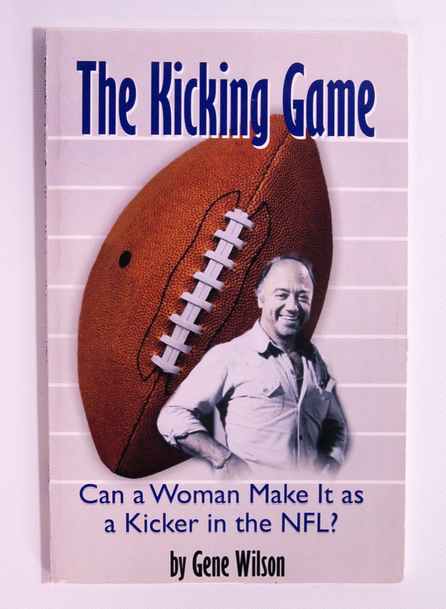 A white page with the words The Kicking Game in big blue letters at the top. The middle of the page is a giant football with a man in front of it. Under the pictures is the book title, and at the very bottom is the authors name in black letters.