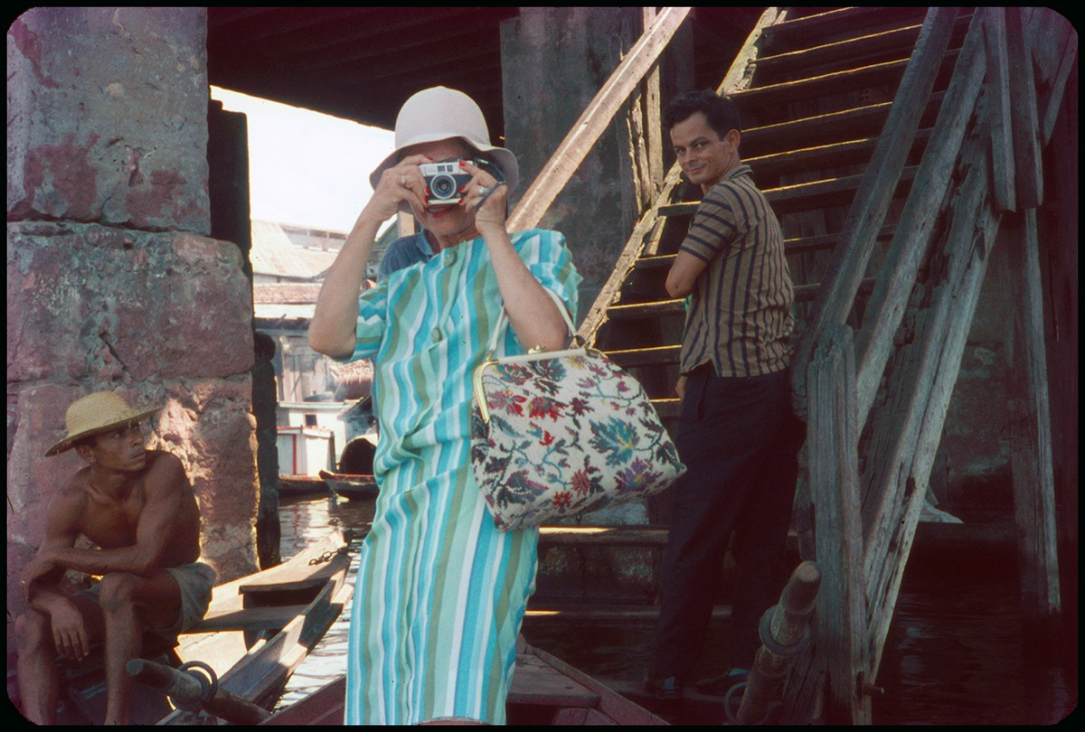 A woman in a light blue striped suit and a white floral handbag holds a camera over her face so that none of her face is seen. She wears a white hat, a man on the right side of the photo is seen climbing the stair and looking towards her. On the left of the photo is a man in shorts and no shirt, wearing a hat.