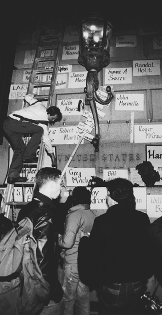 Black and white photo of a man climbing a ladder against a wall that has different papers with names on it. Behind him people are seen watching, a lamp being lit.