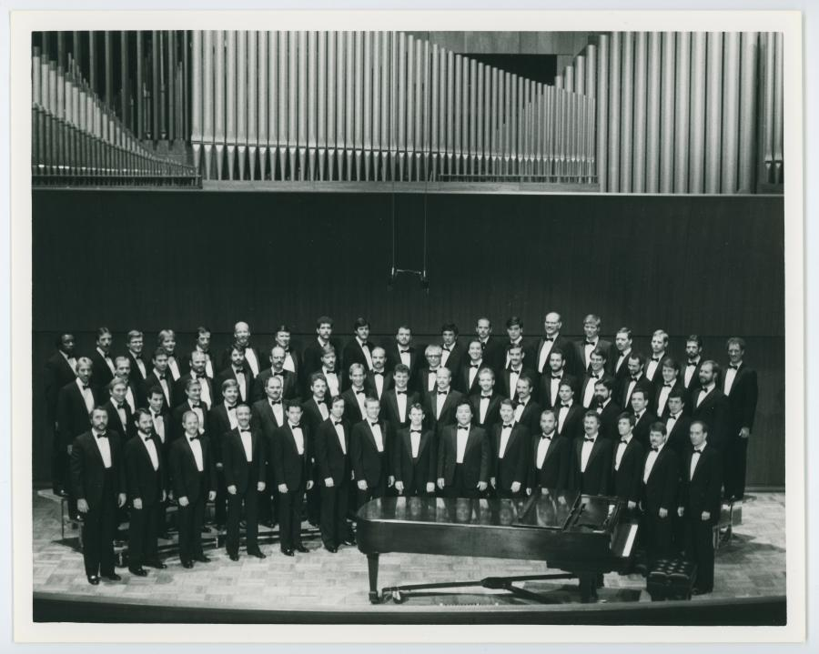A black and white photo of 4 rows of men in a choir in black suits. There is a piano in front of them.