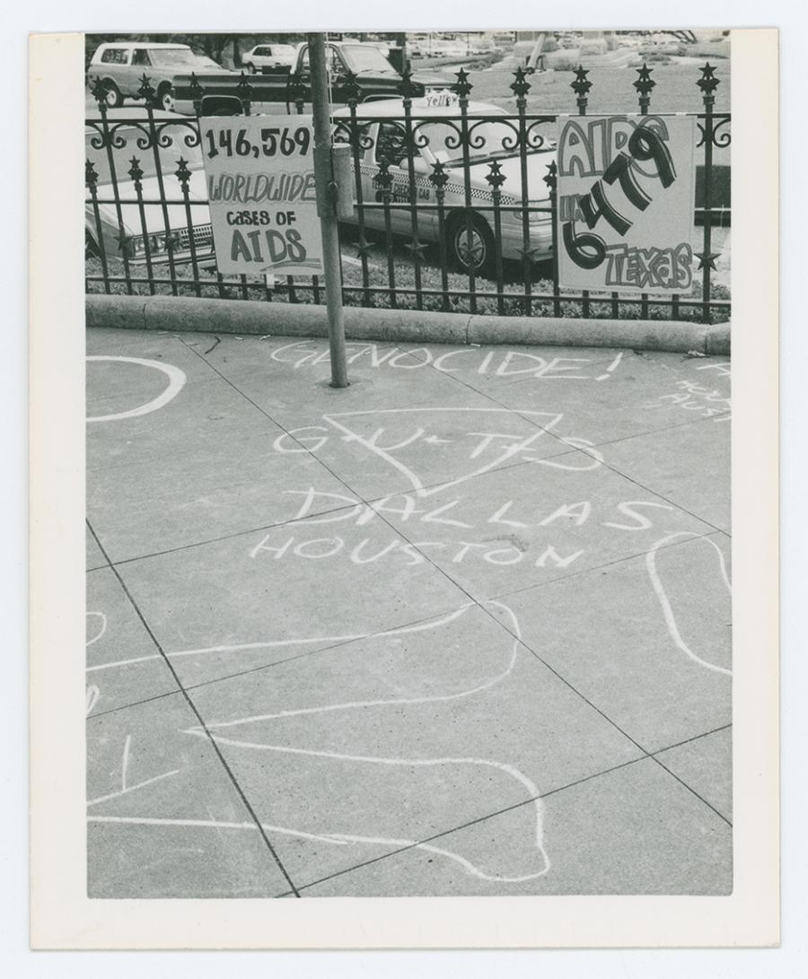 A black and white photo of a sidewalk with chalk on it. Words such as Genocide and Dallas are seen.