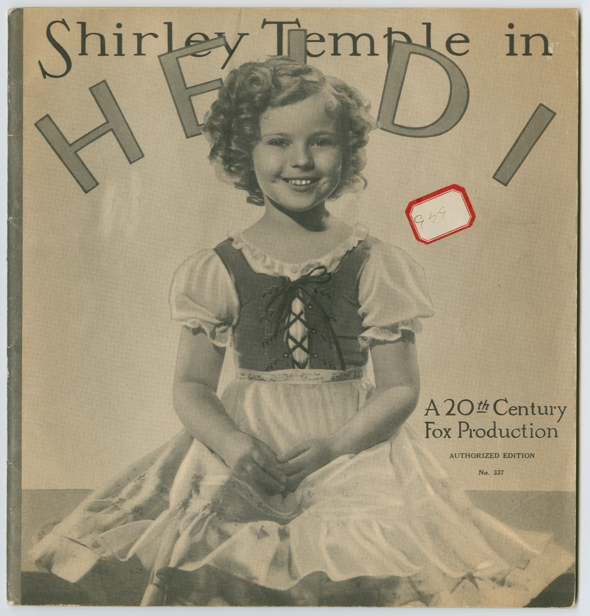 Cover of a publication with a black and white photo of a young Shirley Temple smiling, wearing a dress with a corset tied in the front, with short white sleeves and a white apron.