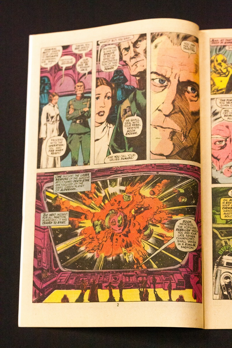 A comic book page with three panels on the top half of the page, and a single panel covering the bottom half.