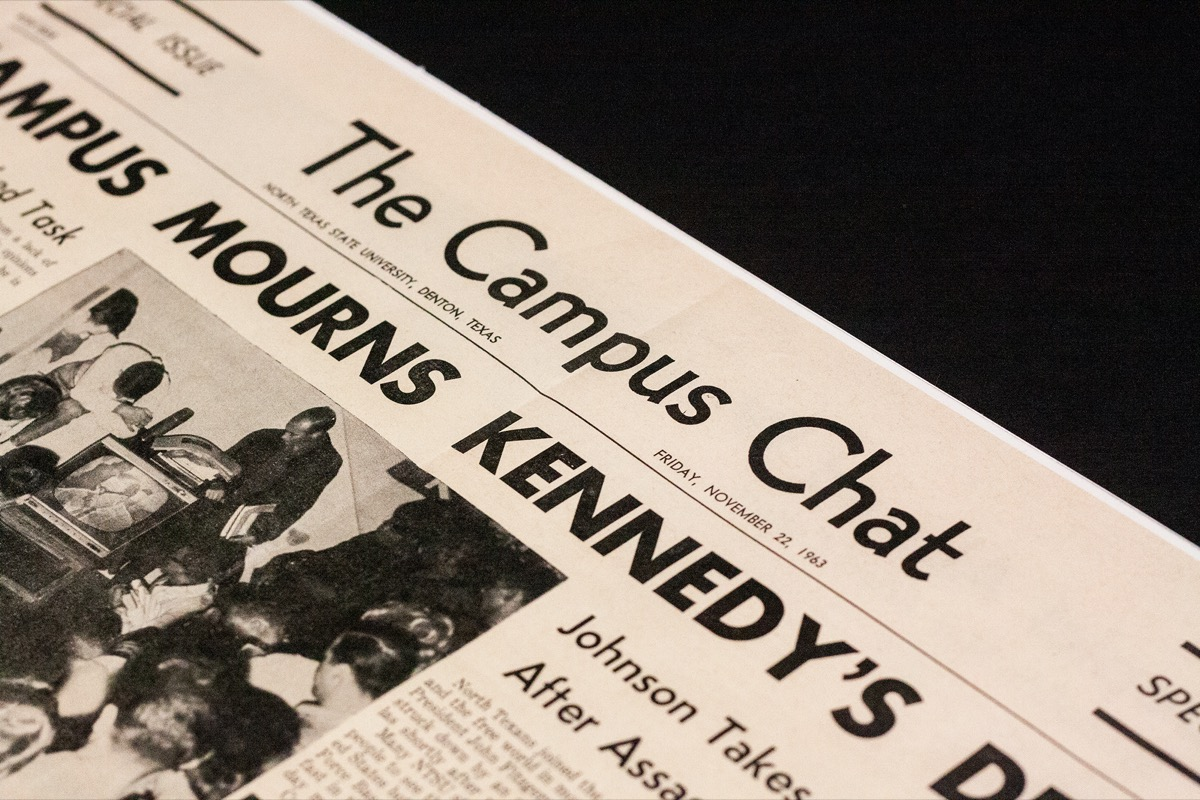 Closeup of a newspaper page. The top of it is titled The Campus Chat, Mourns Kennedy's is shown as part of the title, and a partial photograph.