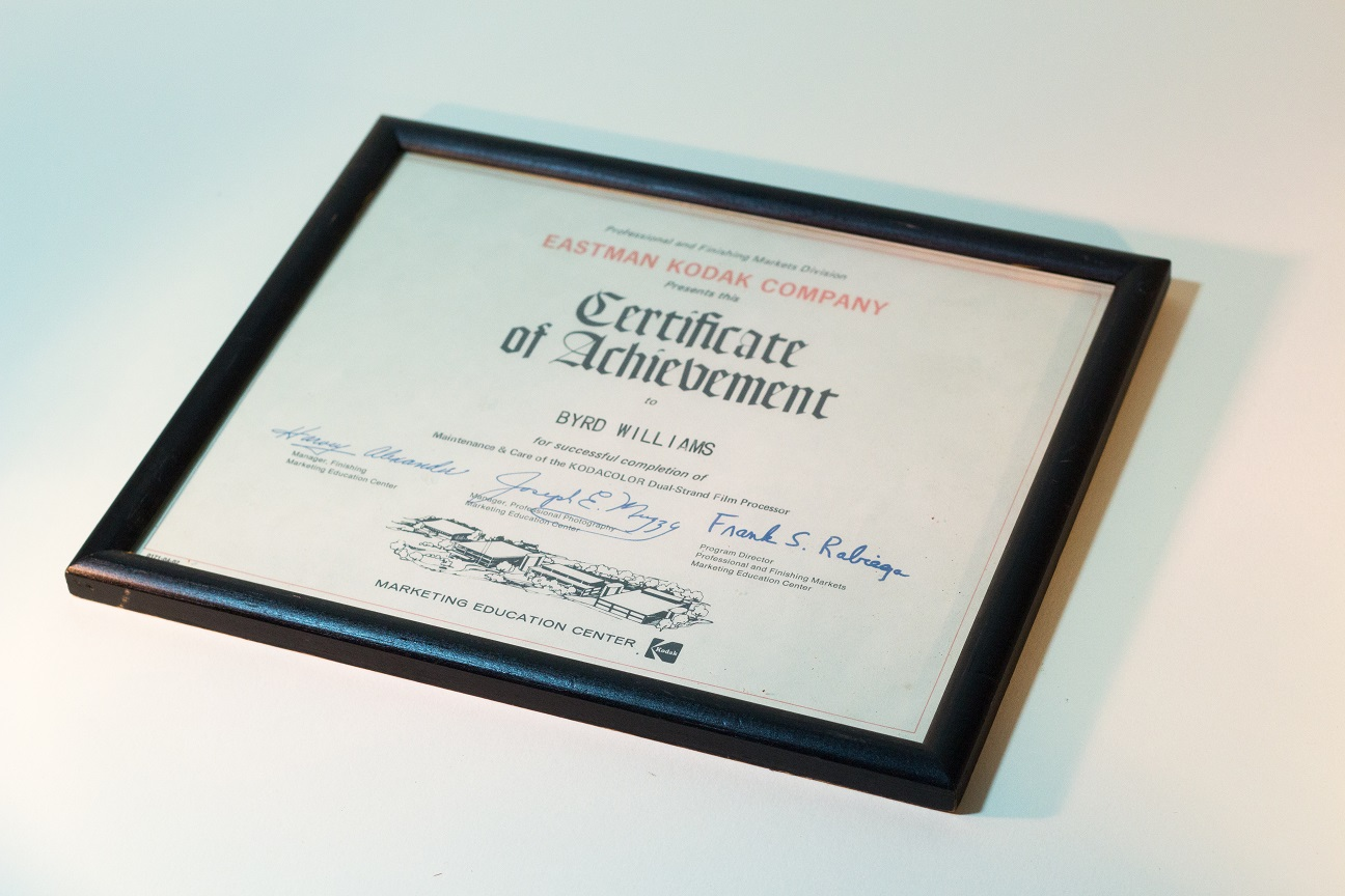 A black framed certificate. The certificate is white with black ink. There are three signatures on it.