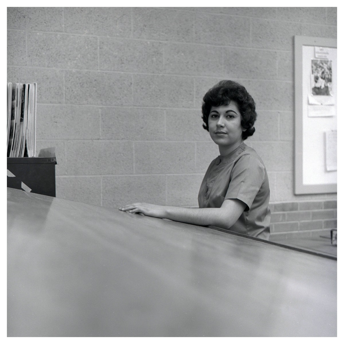Black and white photo of a woman with short hair sitting behind a long desk.