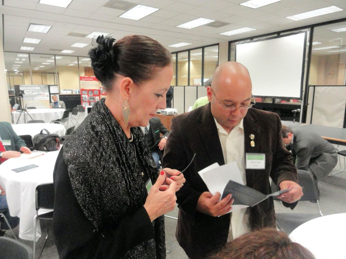 A woman with her hair in a tight bun and a black coat stands next to a bald man with glasses and wearing a suit. They are both looking at a paper in the mans hand.