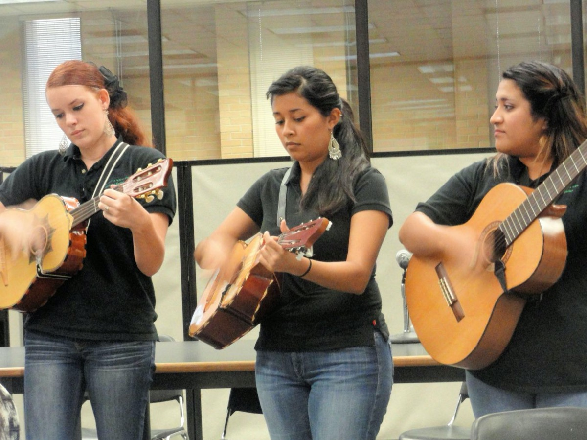 3 women stand next to each other in black shirts and jeans, each with a guitar in hand and strumming it.