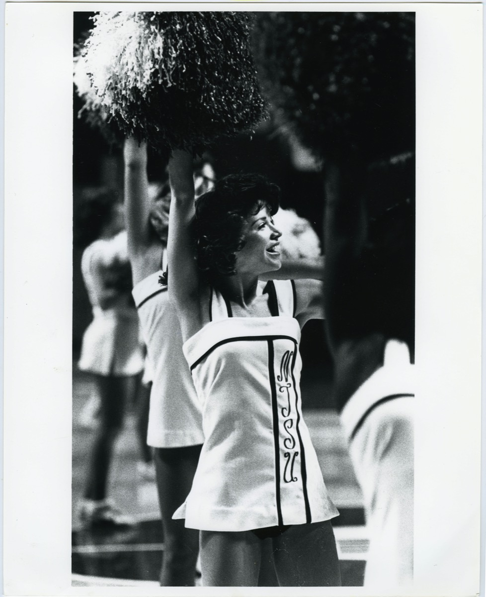 Black and white photo of cheerleaders in a white unifroms. Their hands with pom poms are in the air. The picture is focused on one of them with short curly hair.