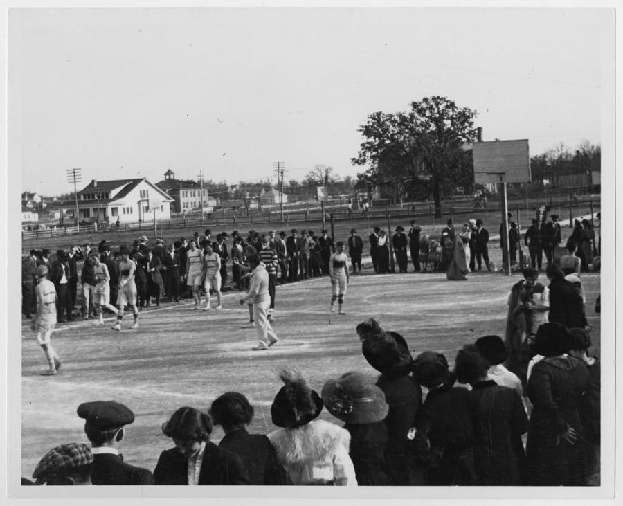 Black and white photo of men in sport uniform on a basketball court. They are completely surrounded by a crowd of onlookers. In the background of the picture is a white building and another field.