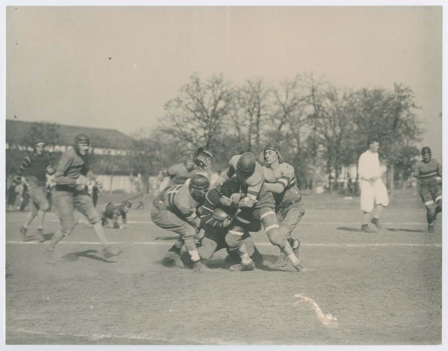 Black and white photograph of 4 men in football uniform ganging up on each other. On the left side is another man in uniform. A man in all white is seen on the right.