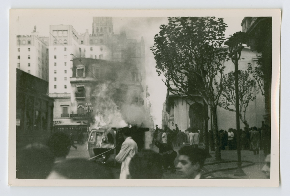 Black and white photo of a building, with a bus burning in front of it. There is a tree on the right side of the photo, people around it.