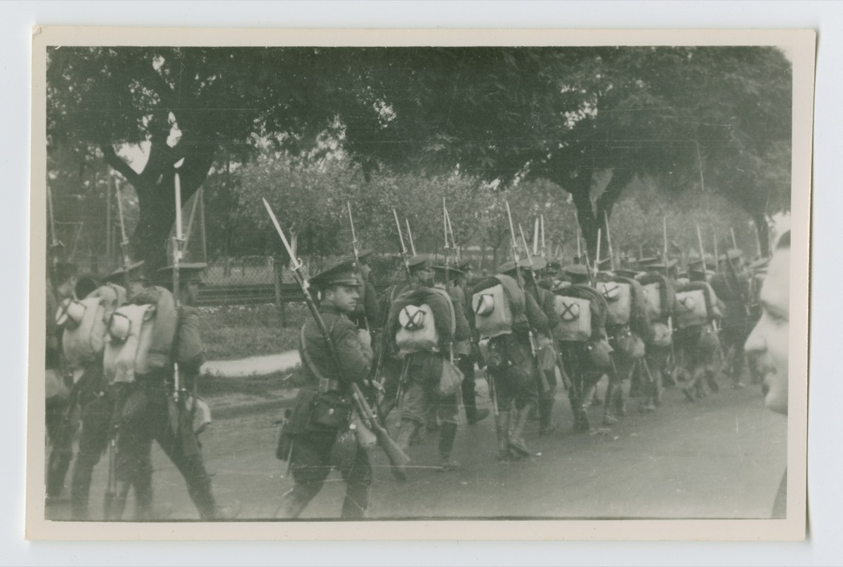 Black and white photo of men in military uniform marching in a line on a street.