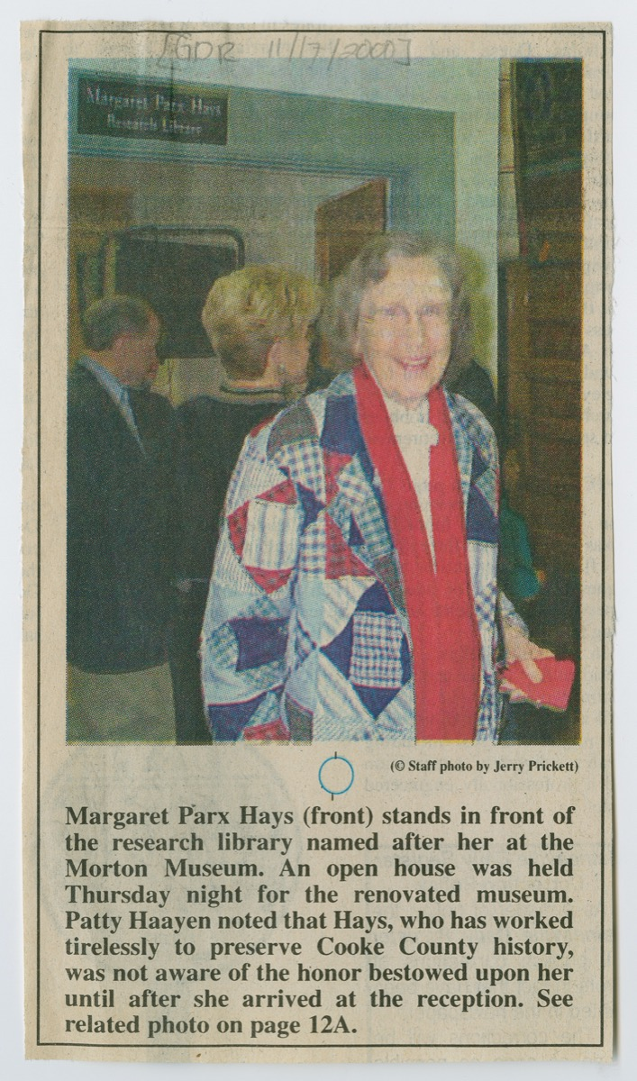 A newspaper clipping, a photo at the top of an older woman with a patched coat, blue and red. Under it is a paragraph of text.