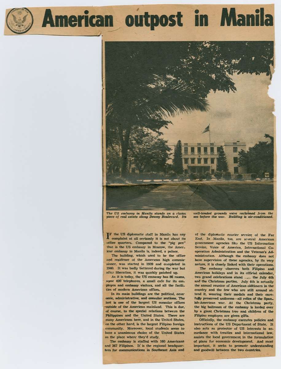 Newspaper clipping titled at the top in bold letters. The left side of the page is cut out, the right side is a photo of a building with a US flag in front of it. Under it are two columns of text.