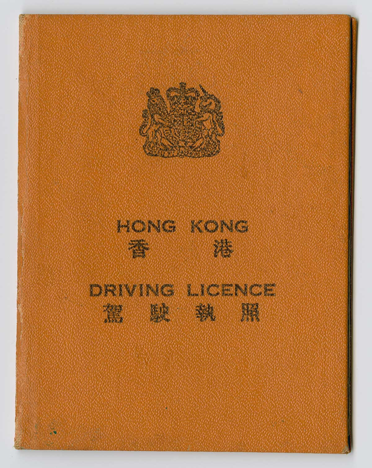 A dark orange booklet, a chinese symbol at the top. Under it are the words Hong Kong and Driving License.