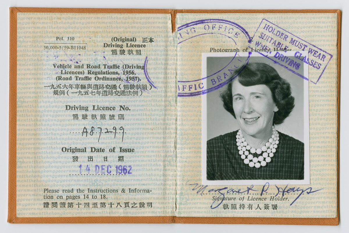 Small open book, the left side with text in English and chinese. The right side is a black and white photo of a woman.